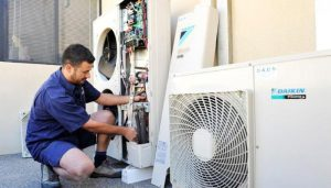 Air Conditioning Service - Man repairing an AC
